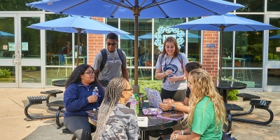 Students at umbrella table outside Cafe Metro