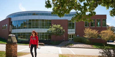 A female student walks past the student center at Penn State Greater Allgheny