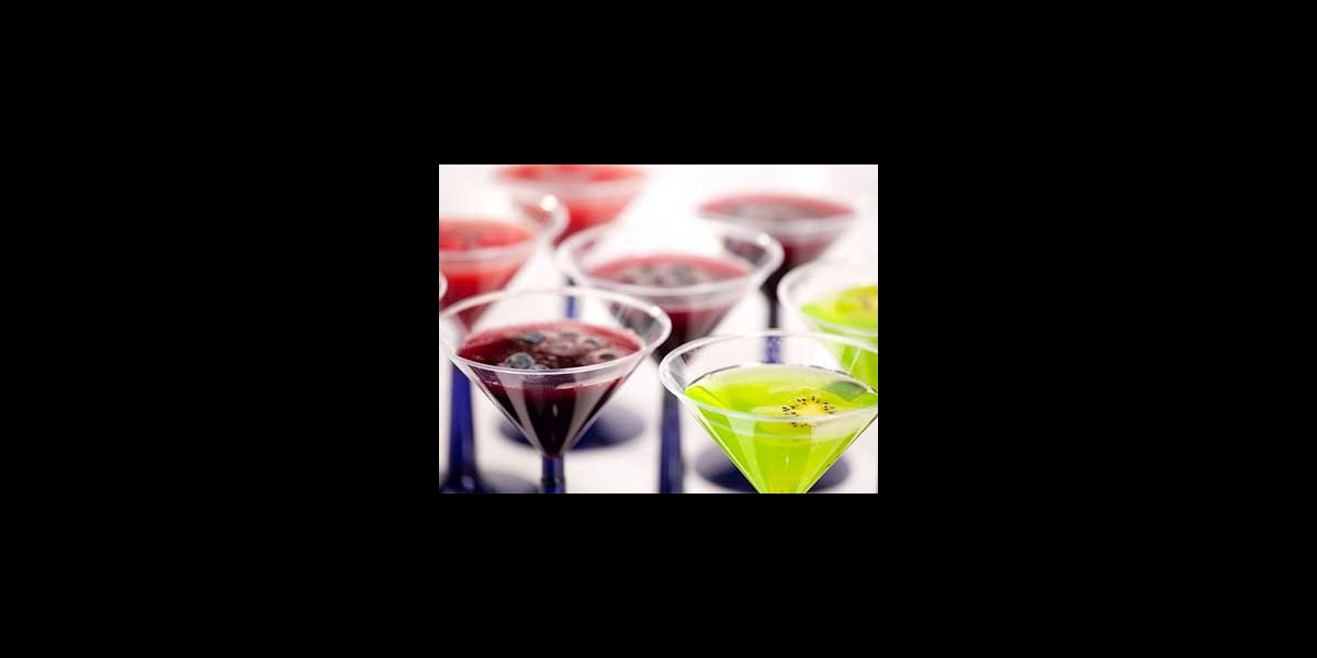 Cocktail glasses filled with red, purple, or green fruit punch