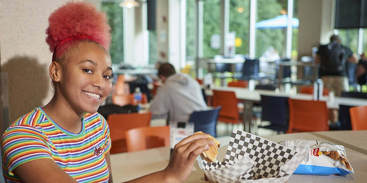 smiling female student eating at Cafe Metro