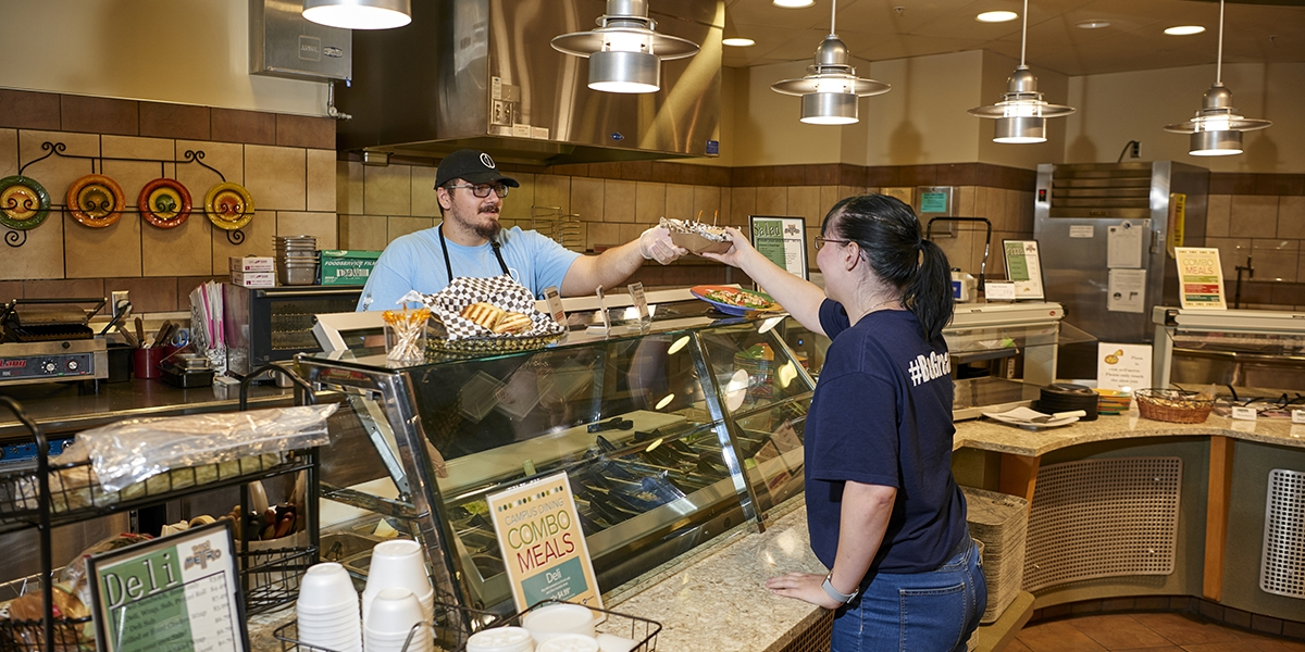 student employee handing food to guest at Cafe Metro