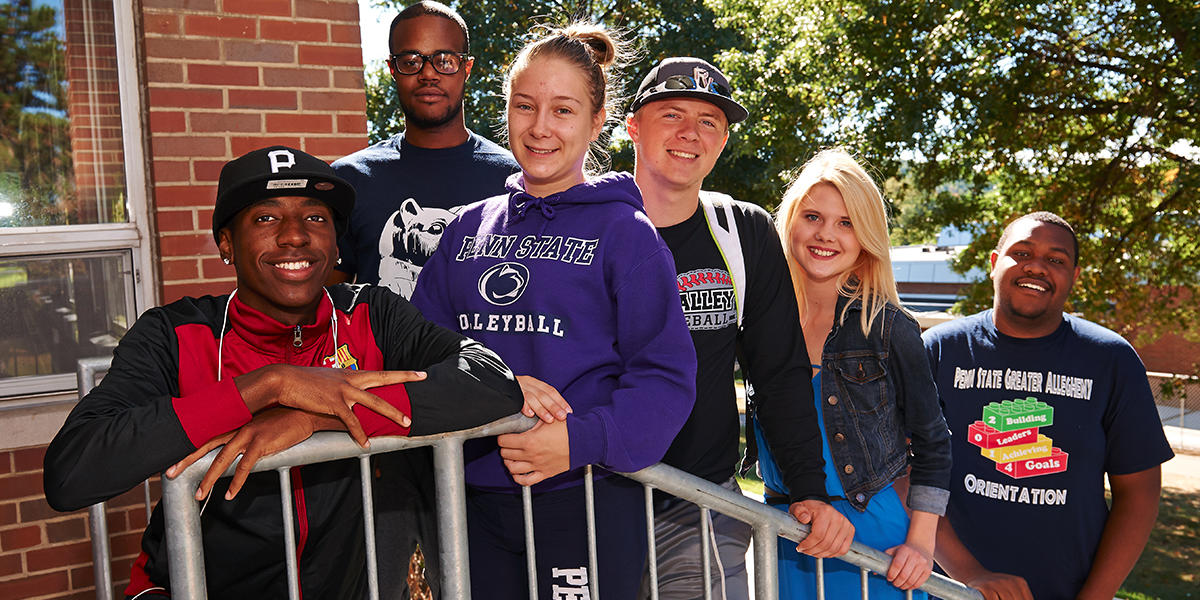 A group of students stands on the steps of McKeesport Hall at Penn State Greater Allegheny