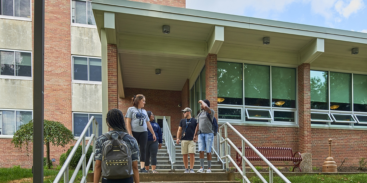 Students on McKeesport Hall exterior stairway to entrance