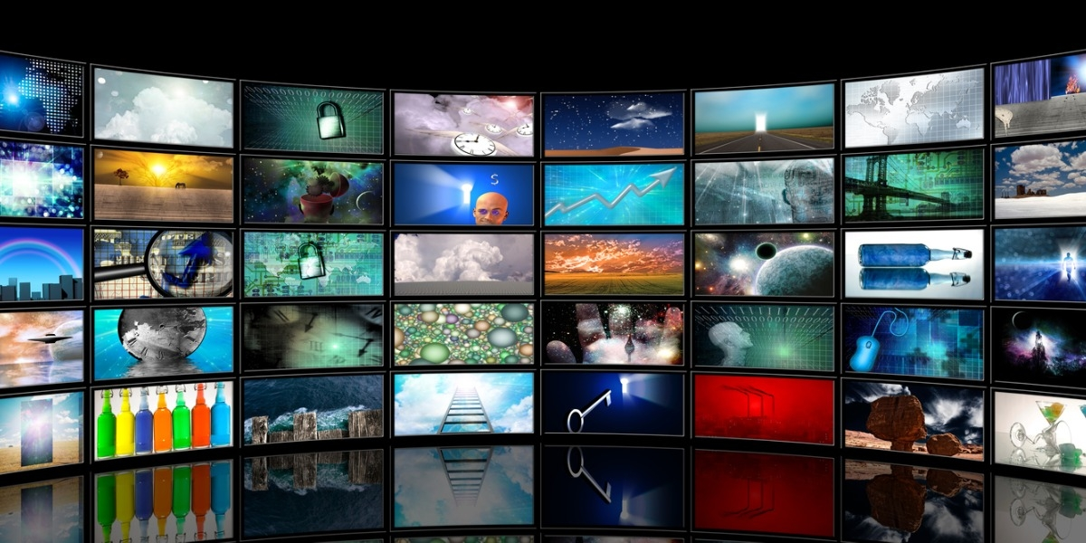 dozens of tv screens arranged in a semi-circle and showing different channels